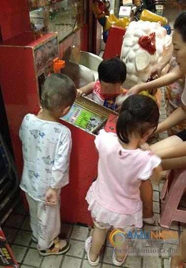"""长沙河西银双路某小区的小超市前,几名幼童在玩""""小钢珠""""机。"""